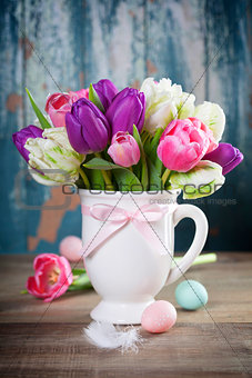 Beautiful tulips bouquet and easter eggs  on wooden table