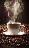 Hot cup of coffee on beans background