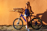 Pretty young hipster blonde girl posing with cycle