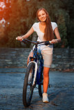Young blonde stylish woman posing with bike