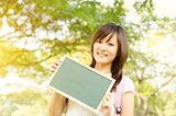 Young Asian college girl student showing blank chalkboard