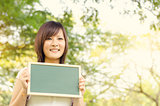 Young Asian college girl student holding blank chalkboard