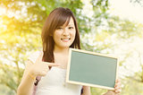 Asian college student showing blank chalkboard