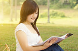 Young Asian college girl student reading book