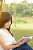 Young Asian college student reading book