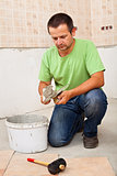 Man installs ceramic floor tiles - preparing the adhesive