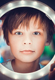 Surprised boy looking at the camera through a luminous circle as an astronaut
