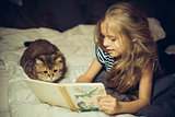 Smiling girl reads book to a cat