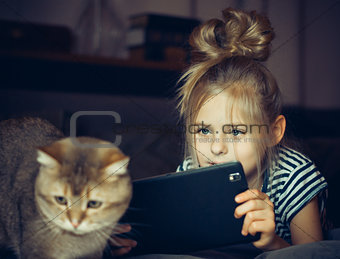 Beautiful girl holding a Tablet and looks at the cat