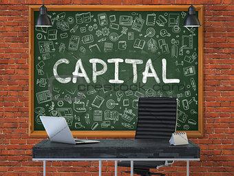 Capital on Chalkboard in the Office.