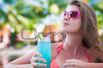 Beautiful woman with tropical cocktail in the pool