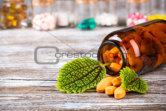 Alternative medicine in glass containers with green leaves