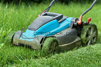 Blue lawnmower cutting grass - closeup