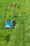 Freshly cut grass strips and blue lawnmower