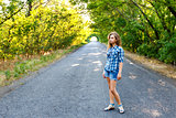 beautiful girl walking on an empty road between green trees