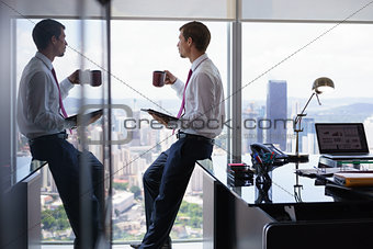 Business Man Drinking Coffe And Reading News On Tablet