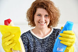 happy woman in rubber gloves with cleaning agents