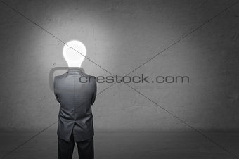 Man in a business suit stands with his back, before him empty concrete wall. Instead of head businessman lighting bulb. Idea concept.