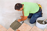 Man laying ceramic tiles floor - spreading the adhesive