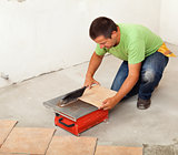 Man cutting ceramic floor tile