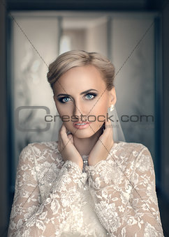 Blond bride with blue eyes in a white dress