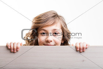 little girl looks from behind a board
