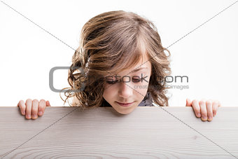 little girl appearing behind a board and looking down