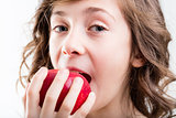 girl eats red apple on white background