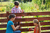 Woman and kids painting the garden fence