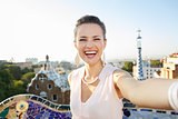 Woman tourist taking selfie in Park Guell, Barcelona, Spain