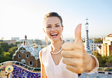 Woman tourist showing thumbs up in Park Guell, Barcelona, Spain