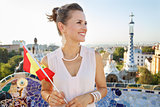 Smiling woman tourist with Spain flag in Park Guell, Barcelona