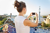 Seen from behind woman taking photo in Park Guell, Barcelona