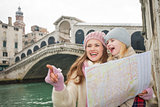 Mother pointing daughter on something near Ponte di Rialto