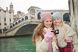 Mother showing photo to daughter in front of Rialto Bridge