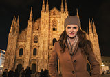 Young woman in coat standing in front of Duomo in evening, Milan