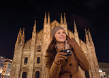 Happy woman with photo camera near Duomo in evening, Milan