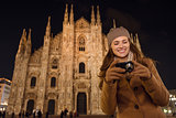 Woman looking on photos in camera near Duomo in evening, Milan