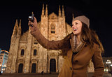 Smiling woman taking photos in front of Duomo in evening , Milan