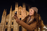 Woman with photo camera pointing on something near Duomo, Milan
