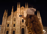 Young woman taking photo of Duomo in the evening, Milan
