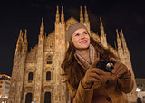 Smiling woman with photo camera near Duomo in evening, Milan