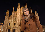 Happy woman talking cell phone near Duomo in evening, Milan