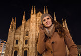 Young woman talking cell phone near Duomo in evening, Milan
