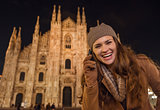 Smiling woman talking cell phone near Duomo in evening, Milan