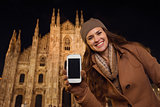 Smiling woman showing cell phone near Duomo in evening, Milan