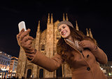 Smiling woman taking selfie in front of Duomo in evening, Milan