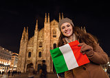 Smiling woman showing Italian flag near Duomo in evening, Milan