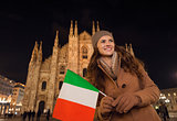Smiling woman with Italian flag near Duomo in evening, Milan