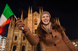 Smiling woman waving Italian flag near Duomo in evening, Milan